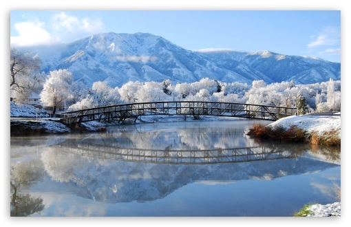bridge by mountain and lake in winter